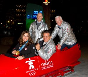 Gold Medal winner Maelle Ricker, and OMEGA President Stephen Urquhart in bobsleight, standing in the back is Astronaut Tom Stafford and in the back is Astronaut Gene Cernan