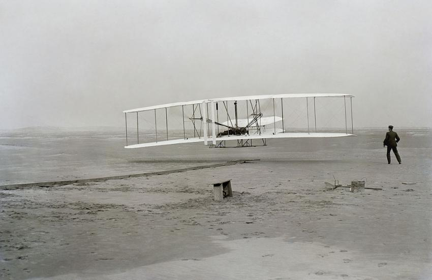 """Picture taken of the first successful flight of the Wright Flyer. The machine traveled 120 ft (36.6 m) in 12 seconds at 10:35 a.m. at Kill Devil Hills, North Carolina. Orville Wright was at the controls of the machine, lying prone on the lower wing with his hips in the cradle which operated the wing-warping mechanism. Wilbur Wright ran alongside to balance the machine, and just released his hold on the forward upright of the right wing in the photo. The starting rail, the wing-rest, a coil box, and other items needed for flight preparation are visible behind the machine. This is described as """"the first sustained and controlled heavier-than-air, powered flight"""" by the Fédération Aéronautique Internationale, but is not listed by the FAI as an official record. (Source: Wikipedia)"""