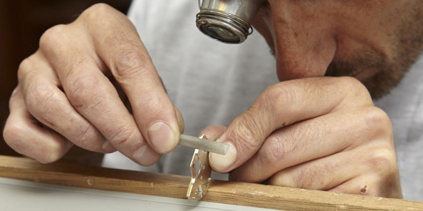 A watchmaker finishing a bridge at Garrick's workshop