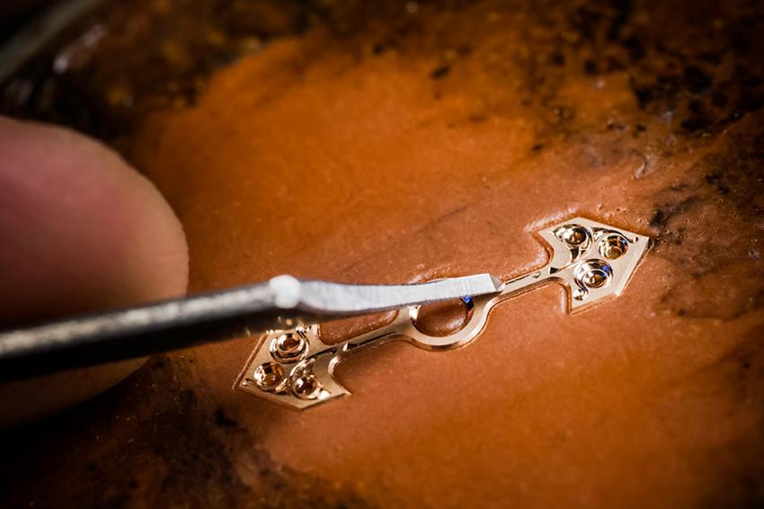 engraving the gold bridge of the tourbillon of the Girard-Perregaux Cat's Eye Tourbillon.
